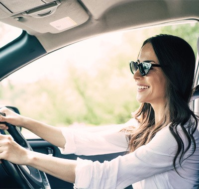 a woman wearing sunglasses driving a car